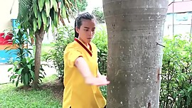 MA asian girl kicking a tree